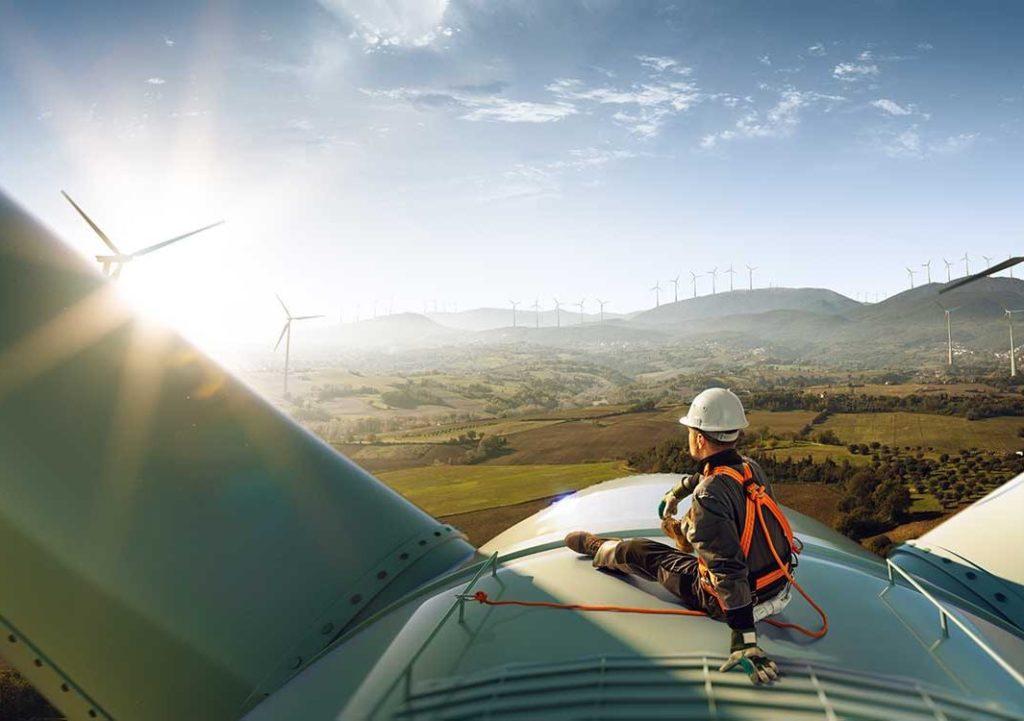 Happy engineer sits on top of wind turbine