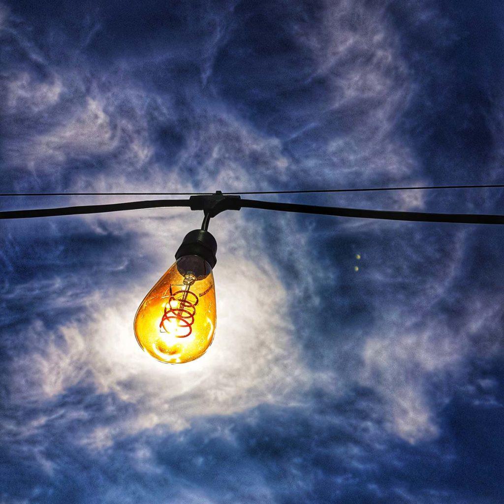Lightbulb hanging against a blue sky