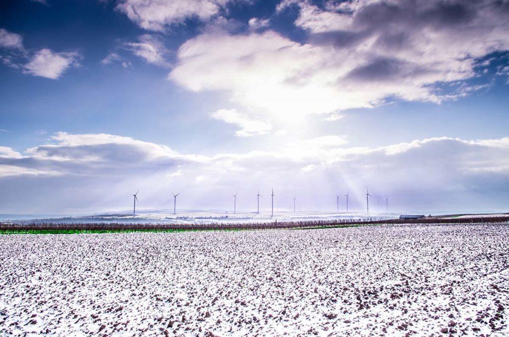 Wind turbines on horizon over snowy field and under bright sun